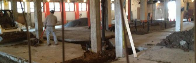 Construction photo of Houston Gym showing the existing floor slab cut with trenches
