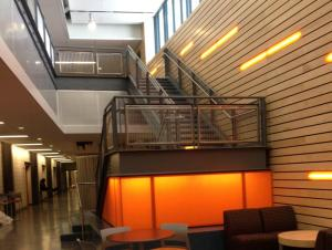 Technology Building - seating area in lobby with open stair and wood slat wall to the right